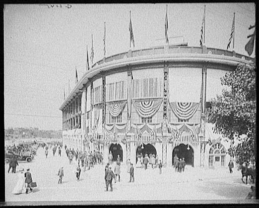 Dozens of men and women approach Forbes Stadium.  A few cars are parked to the left side.  Black and white, c1910.