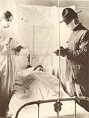 A military doctor and nurse wearing masks treat a sick patient who is lying in bed.