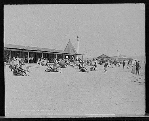 Numerous sunbathers sit or walk on the beach in a black and white image of Easton Beach in Newport, Rhode Island.