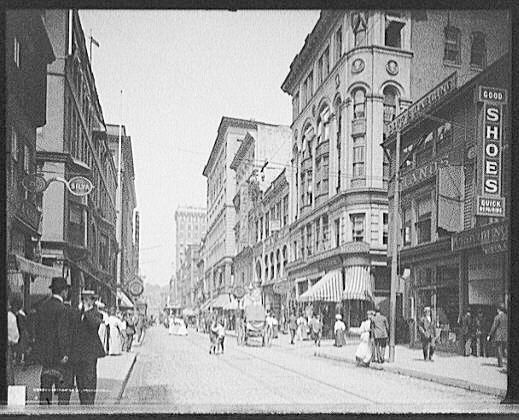 Numerous men and women go about their business in a busy street in c1906 Providence Rhode Island.  Several buildings and a horse-drawn carriage are visible in the background.