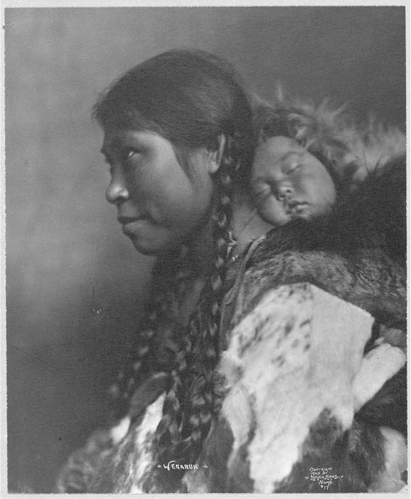 An Eskimo mother is shown in profile with her child sleeping on her back.