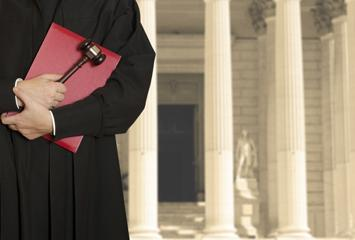 A judge holds his gavel and law book in front of a courthouse.