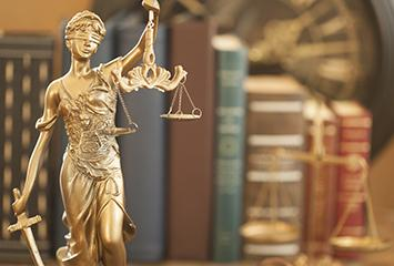 A statue of lady justice profiled in front of law books.