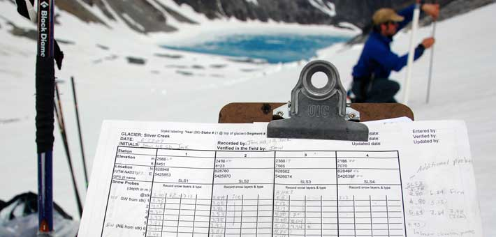 Photo of a glacier monitoring data sheet on a clipboard with a researcher in the background (Photo by Jim McLeod)