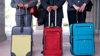 Business people standing with suitcases - Thinkstock image