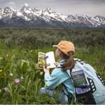 Child reading in front of the Teton Range.