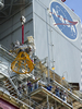 Stennis Space Center engineers and technicians watch as the J-2X powerpack is hoisted into place on the A-1 Test Stand.