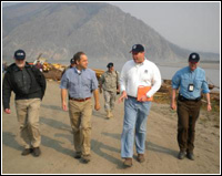 Alaska Governor Sean Parnell (center left) is briefed on recovery progress by FEMA Federal Coordinating Officer Doug Mayne (center right). Of the community's 58 residences, 13 were destroyed and 8 were damaged, in addition to multiple businesses damaged or destroyed. - Jack Heesch/FEMA