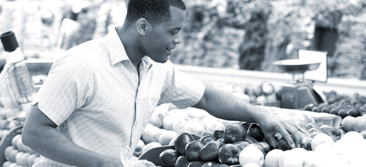 Photo of a man picking through produce at a grocery store