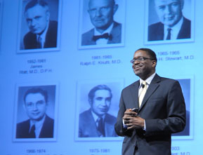Photograph of Dr. Gary Gibbons giving a speech to the NHLBI community, with a digital presentation displayed behind him (showing the previous NHLBI directors).