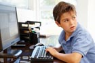 A young boy sits at a computer