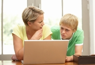A mother and son look at a computer