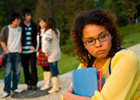 A girl stands apart from other teens
