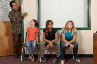 Students sit outside the principal's office