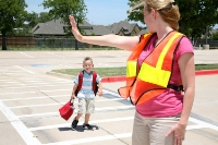 A crossing guard helps a child