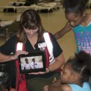 Photo: LaPlace, La., Sep. 7, 2012 -- Mar Tobiason, Red Cross shelter volunteer, shows a group of children a YouTube video featuring children living in a temporary shelter. The American Red Cross and FEMA are working with local, state and other federal agencies to assist residents affected by Hurricane Isaac.
