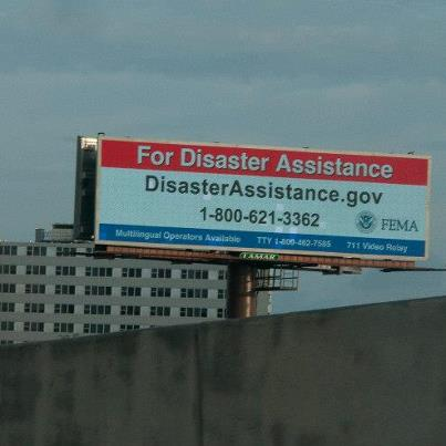 Photo: New Orleans, La., Sep. 4, 2012 -- A billboard near the I-10 Freeway in New Orleans, La., lists the contract information for FEMA registration. FEMA is working with the private sector to insure that Hurricane Isaac survivors are able to receive this registration information.