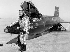 Neil Armstrong standing in front of  X-15 on lakebed