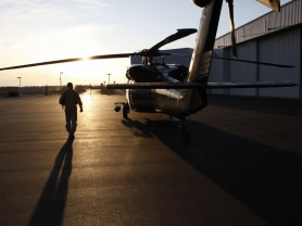 A CBP pilot approaches a helicopter