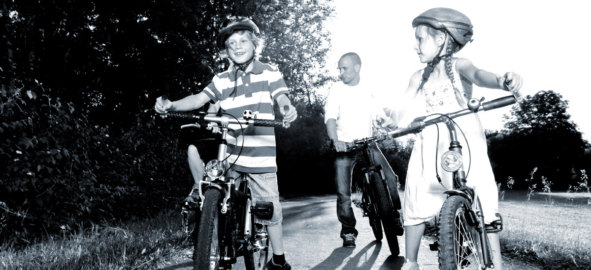 Photo of a young boy, girl and father riding bikes