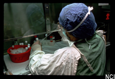 Photograph of a scientist wearing protective gear working at a lab bench