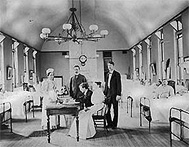1916 photograph of Dr. Joseph Goldberger seated at a table in a hospital surrounded by four assistants