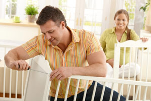 man assembling a crib while a pregant woman watches