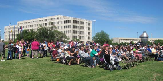 A crowd of people sit outside in rows of chairs at the Oklahoma Systems of Care Community Picnic