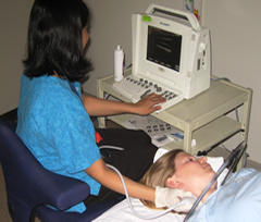 Photo of technician using ultrasound to test the carotid artery of a patient