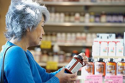 mujer con botella de suplementos