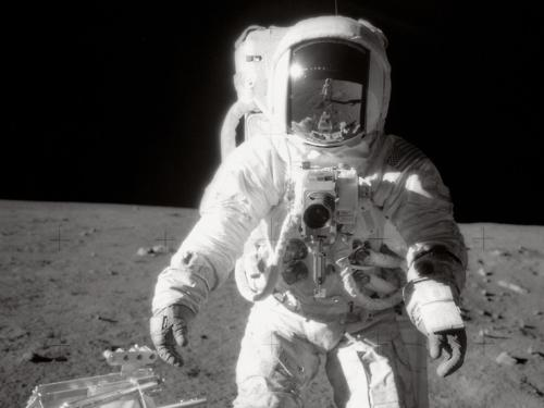 Image description: Astronaut Alan L. Bean pauses near a tool carrier during the Apollo 12 spacewalk on the moon's surface. Commander Charles Conrad, Jr. took the black-and-white photo and is reflected in Bean's helmet visor. Photo by NASA