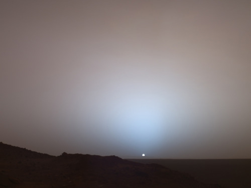 Image description: On May 19, 2005, NASA's Mars Exploration Rover Spirit captured this stunning view as the Sun sank below the rim of Gusev crater on Mars. This Panoramic Camera mosaic was taken around 6:07 in the evening of the rover's 489th Martian day, or sol. From NASA: Sunset and twilight images are occasionally acquired by the science team to determine how high into the atmosphere the Martian dust extends, and to look for dust or ice clouds. Other images have shown that the twilight glow remains visible, but increasingly fainter, for up to two hours before sunrise or after sunset. The long Martian twilight (compared to Earth's) is caused by sunlight scattered around to the night side of the planet by abundant high altitude dust. Similar long twilights or extra-colorful sunrises and sunsets sometimes occur on Earth when tiny dust grains that are erupted from powerful volcanoes scatter light high in the atmosphere. Photo by: NASA/JPL/Texas A&M/Cornell