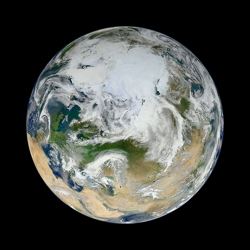 """Image description: From NASA's Earth Observatory: There have been many images of the full disc of Earth from space – a view often referred to as """"the Blue Marble"""" – but few have looked quite like this. Using natural-color images from the Visible/Infrared Imaging Radiometer Suite (VIIRS) on the recently launched Suomi-NPP satellite, a NASA scientist has compiled a new view showing the Arctic and high latitudes."""