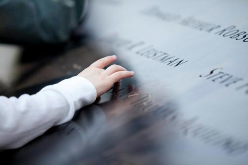 Image description: A child touches the name of someone who died on September 11, 2011. The name is part of the memorial at the National September 11 Memorial and Museum. Find a name on the memorial. Photo by Jin Lee. View more of Lee's photos of touching moments at the memorial.