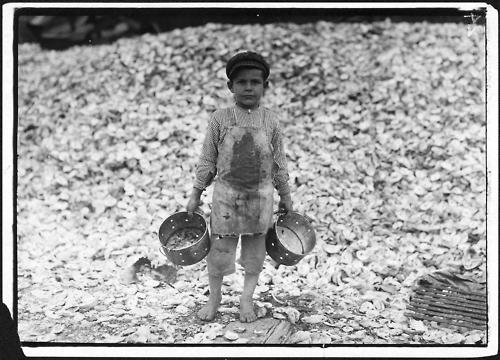 """Image description: A five-year-old child laborer named Manuel stands before a mountain of oyster shells in Biloxi, Mississippi in 1912. This image was part of a series of 5,000 photographs taken by Lewis Hine for the National Child Labor Committee. They were used by the Department of Commerce and Labor's Children's Bureau in both its investigations of child labor issues and advocacy for federal legislation to limit workplace abuses against children. Hines took pictures of children working as harvesters in agricultural field work; pickers in seafood, vegetable, and fruit canneries; workers in cotton mills and glass, furniture, and cigar factories; as """"breaker boys"""" in coal mines; and more. Image courtesy of the National Archives and Records Administration."""