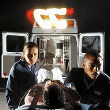 Paramedics wheel a patient out of an ambulance