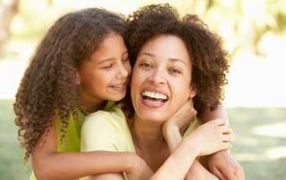 Una niña de cabello rizado abraza a su madre
