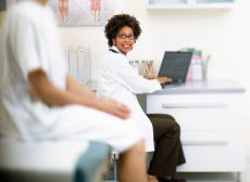 Fotografía de una doctora con una computadora portable y una paciente en un cuarto de examen