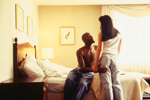 man and woman in a bedroom talking