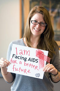 Woman smiling hold sign that says 'I am facing AIDS for a better future