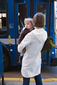 woman holding a baby while waiting for the bus