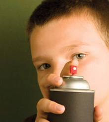 This is a photograph of a boy spraying an aerosol can