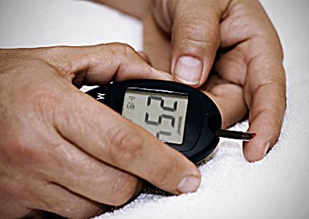 Hands testing finger for blood glucose level.