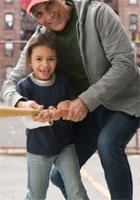 Un abuelo le ayuda a su nieta a usar un bate de béisbol.