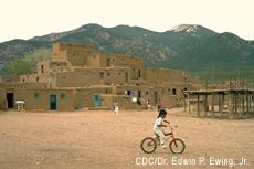 Fotografía de un niño indio norteamericano en bicicleta en el pueblo de Taos de Nuevo México