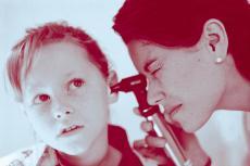 Fotografía de una doctora examinando el oído de una niña