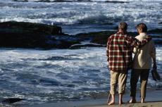 Photograph of a man and woman walking on the beach