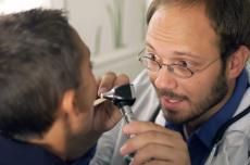 Fotografía de un doctor examinando la garganta de un niño