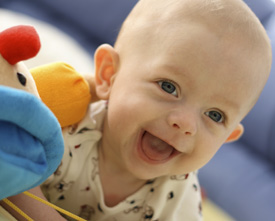 happy baby with soft toy