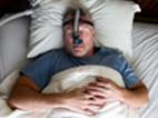 Photo of a man receiving sleep apnea treatment.